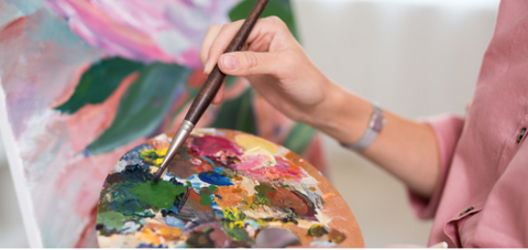 Person dipping a paint brush into a palette of acrylic paint to paint a canvas.