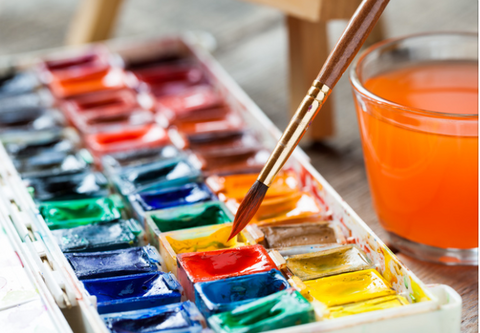 Linear paint brush being dipped into watercolor paint