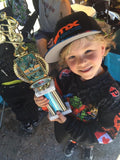 young boy holding a BMX racing trophy