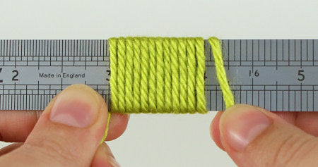 demonstrating wraps per inch, WPI in yarn