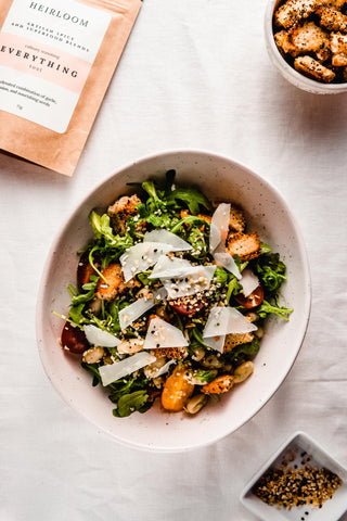 Bowl of salad with white beans, fresh arugula greens, croutons and everything bagel seasoning
