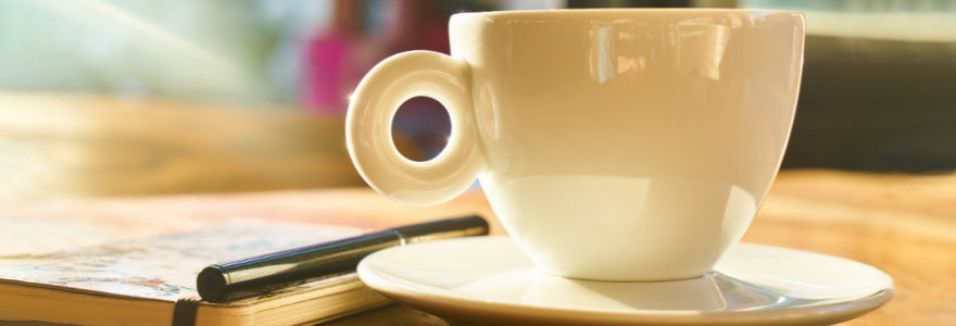 Coffee Cup resting on a plate beside a notebook