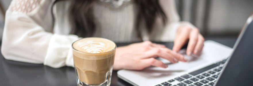 Woman sitting with her coffee in front of a computer