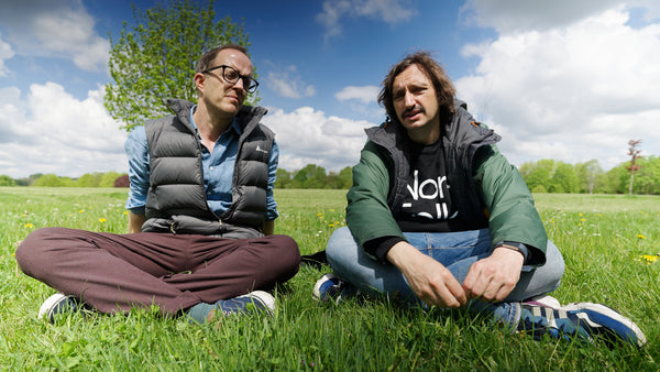 Robbie and Mike sit in a park