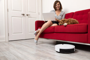 Woman registering for bObi's warranty while bObi Classic robotic vacuum sweeps under the couch.