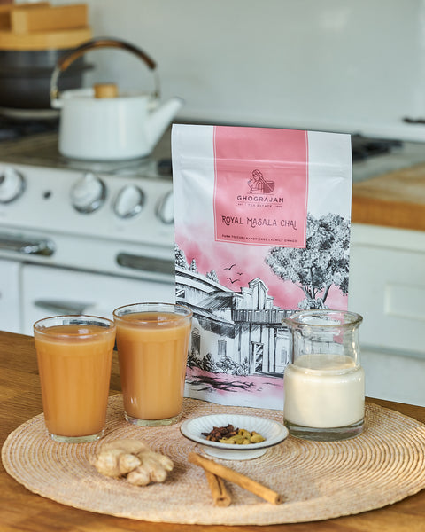 Ghograjan Masala Chai pouch with cinnamon, cardamom, ginger and cloves on the side