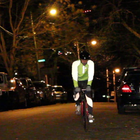 A man in reflective tights and shirt riding a bicycle in the street at night
