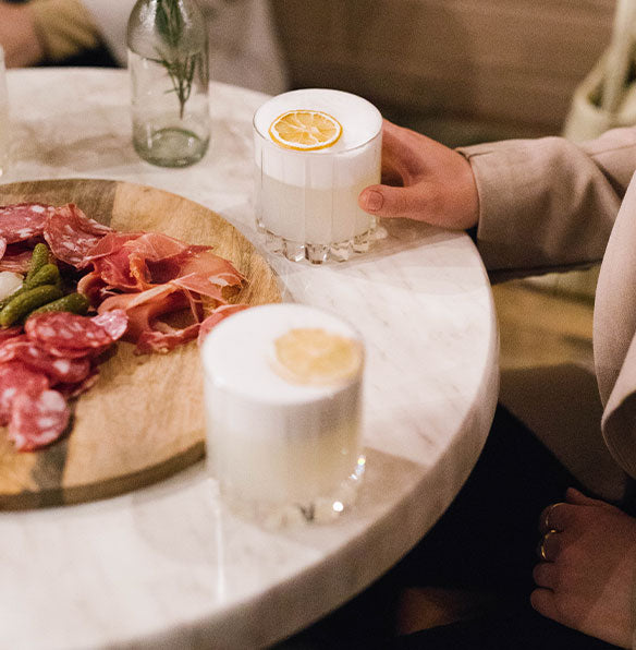Image of two cocktails and an cured meats platter