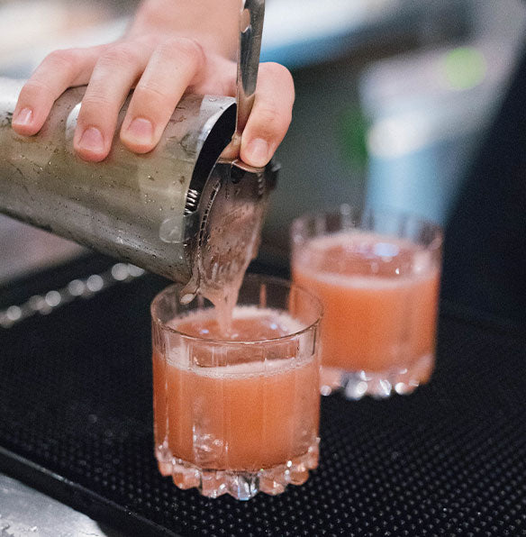 Image of two cocktails being poured from a shaker