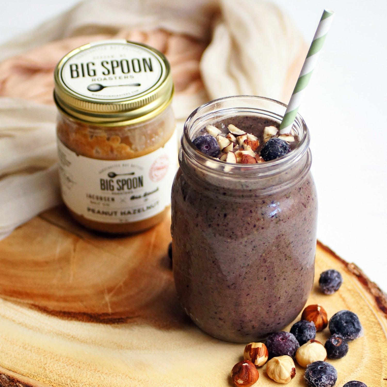 Big Spoon Roasters Peanut Hazelnut Butter next to a jar with a blueberry breakfast smoothie.