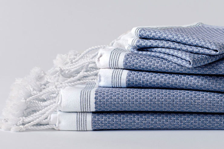 Organic towels woven from yarn-dyed organic cotton and edged in hand-knotted fringe.