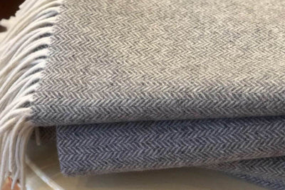 Woven wool comfort, these throws are machine woven in an intricate herringbone pattern.
