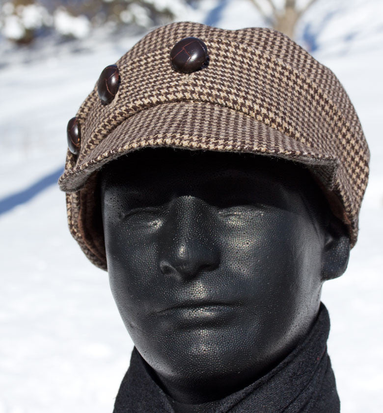 Brown hounds tooth wool tweed hat with leather buttons across the crown.