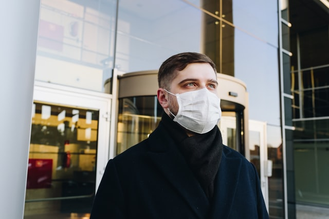 Man wearing a mask who's smelling his own breath.