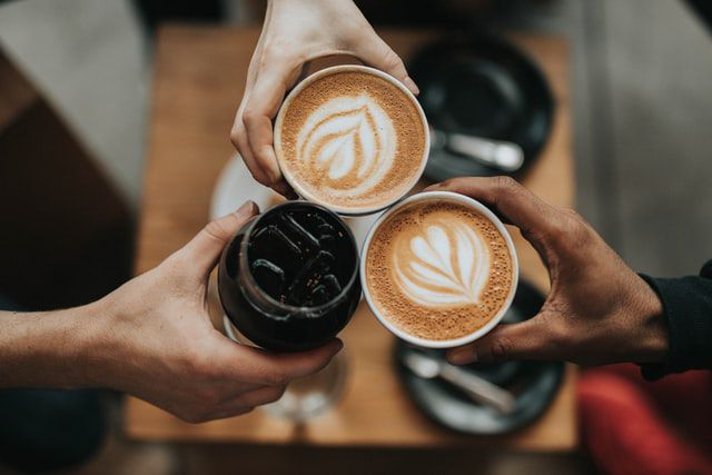 Three hands holding coffee that may cause coffee stains on their teeth.