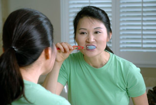 Woman brushing her teeth to remove plaque and tartar.