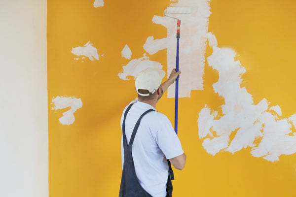 male painter rollering on base coat of previously prepared yellow wall