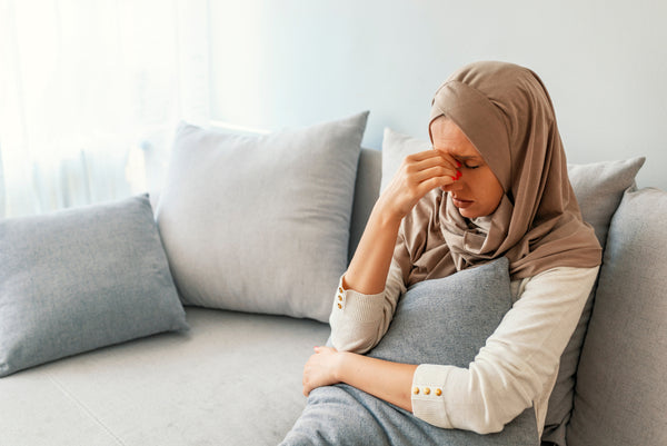 Sad Muslim woman holding her nose and head because of allergic reaction