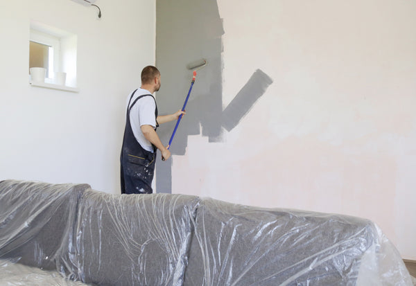 man painting grey over primed painted all