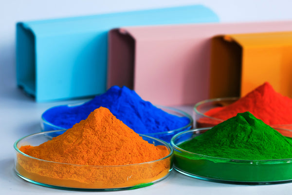 Piles of green, orange, red and blue paint pigment powders in glass plate