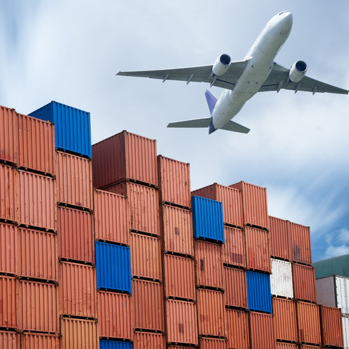 An areophane flying low over a wall of  blue and rust metal cargo containers