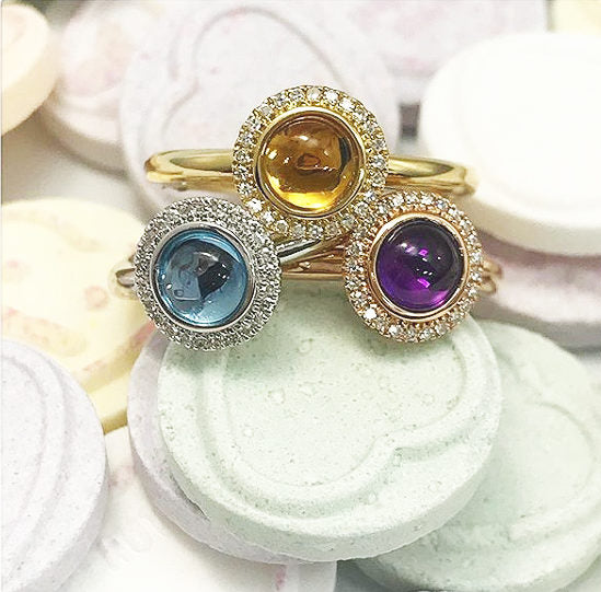 An image of three 18ct gold rings with a stone in the middle and diamonds around it