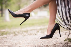 A picture of a woman's legs in heels in a park