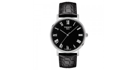An image of a Tissot watch with a black face, white roman numerals and a black leather strap