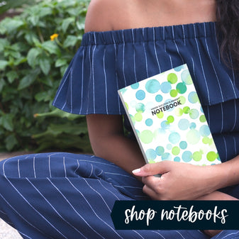 Woman sitting in front of greeenery holding Soda Pop Notebook