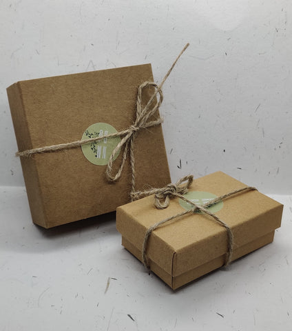 A larger cardboard box on the left and a smaller cardboard box on the right, both wrapped with natural rope and with a No More Boring Jewellery sticker