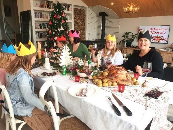 Family sitting at the Christmas table wearing their Waste Free Celebrations reusable cotton crowns.