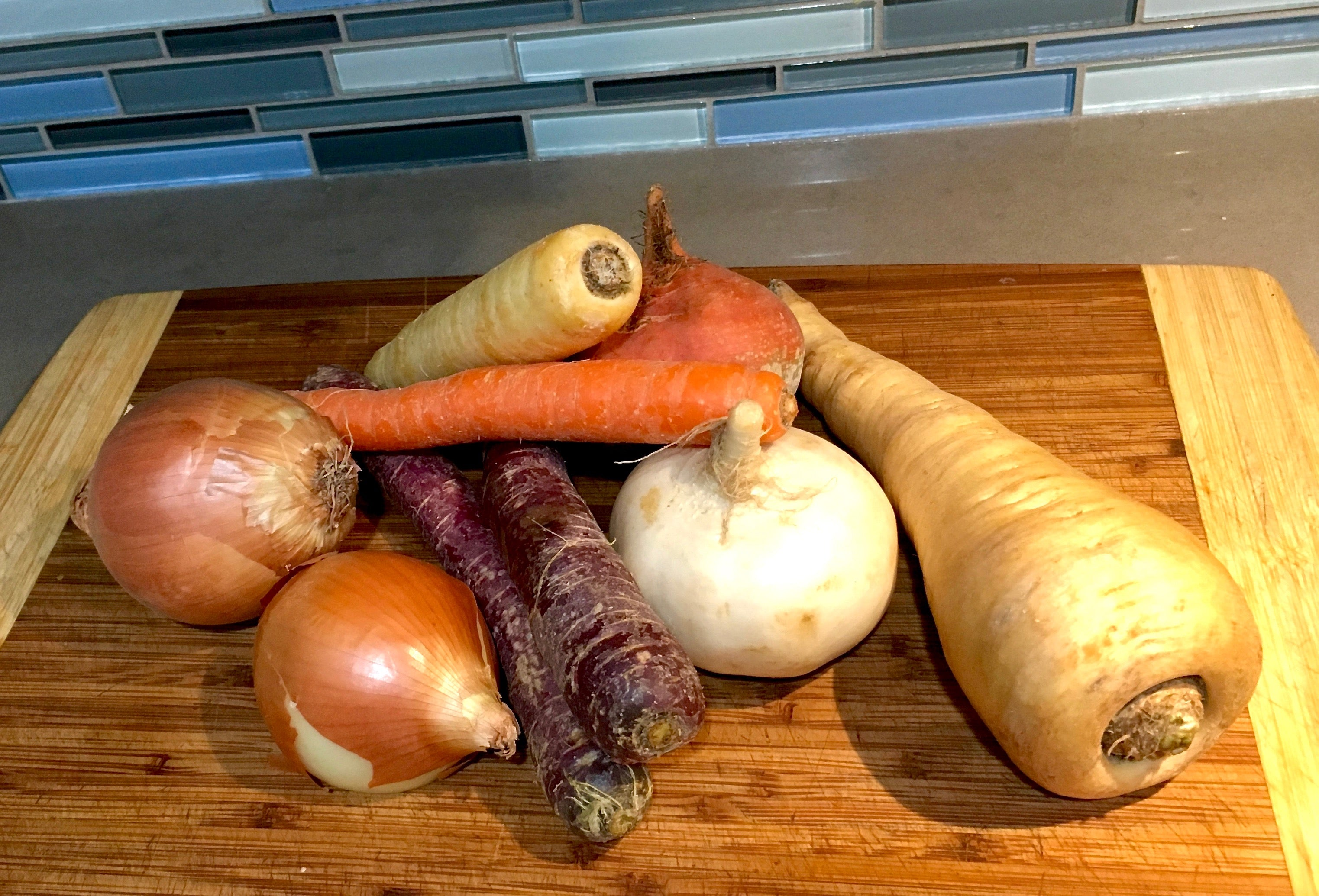 purple carrots, yellow onions, and other fresh produce on cutting board
