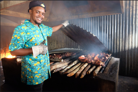 A man standing beside the pimento wood used to cook jerk chicken and jerk pork at Scotchie's Montego Bay, Jamaica