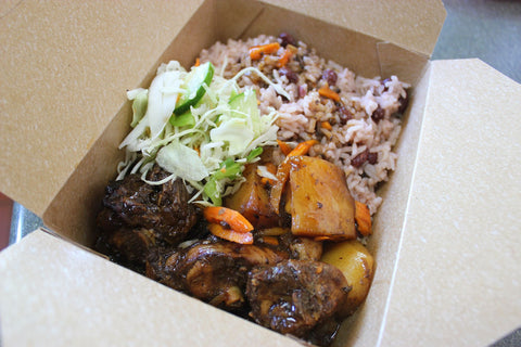 Serving of oxtail, rice and peas, and salad from Island Grill in a take out container.
