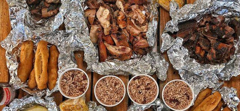 Top view of a table with rice and peas, jerk chicken, jerk pork, festival and red stripe.