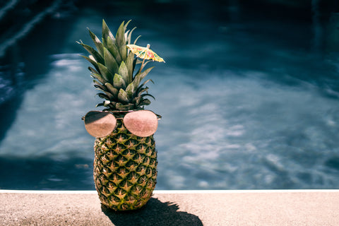 a pineapple placed by pool with sunglasses on and wearing cocktail umbrella