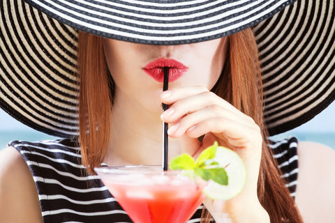 girl wearing hat drinking a cocktail with a straw