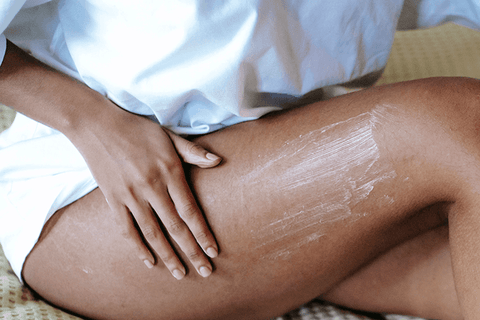 Girl rubbing a slimming cream on her thighs