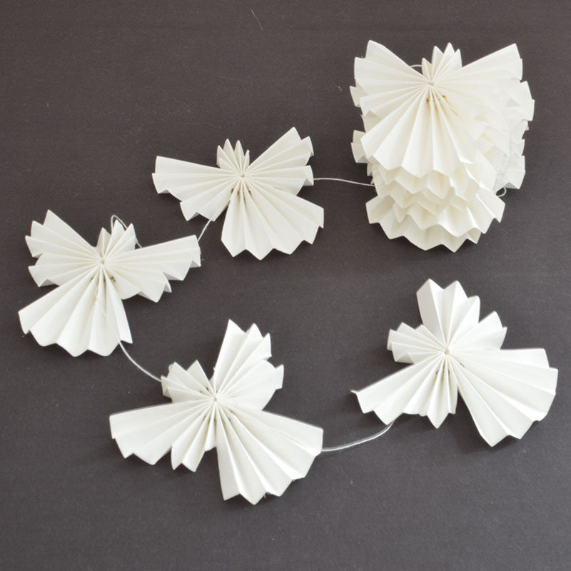 White paper angels christmas decoration on a string on Oates & Co.