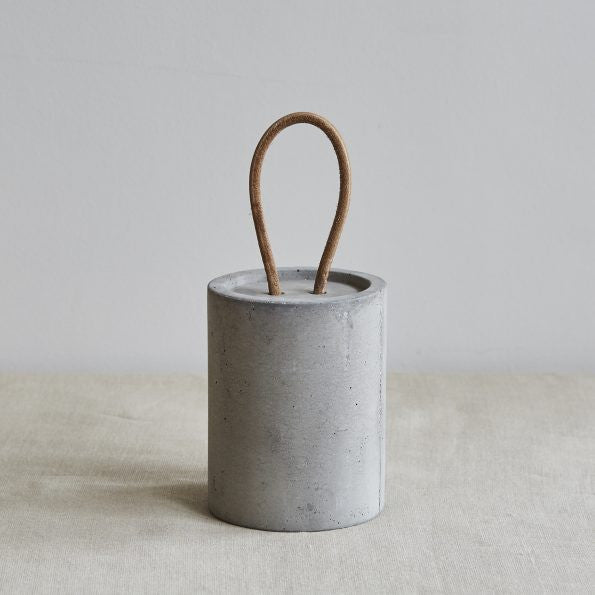 Cylindrical concrete doorstop with leather handle on Oates & Co.