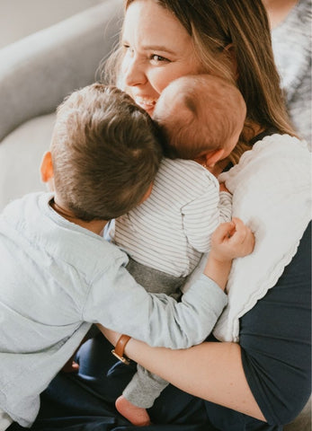 woman hugging baby and a toddler
