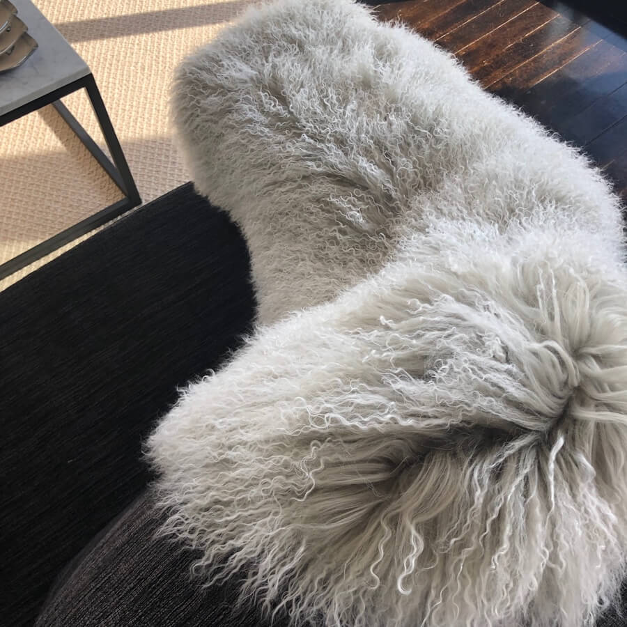 Mongolian sheepskin throw rug in grey with white tips draped over chair
