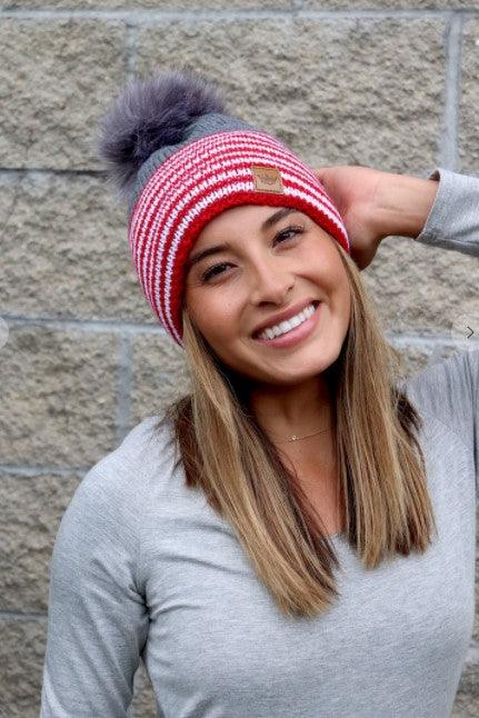 Red and white fleece lined striped hat with grey color block and pom