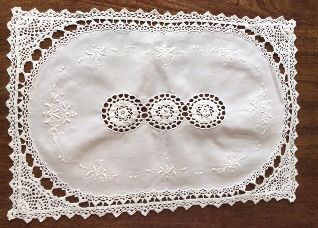 Placemats and Napkins:  White oval embroidered linen placemats set in rectangular border of French lace