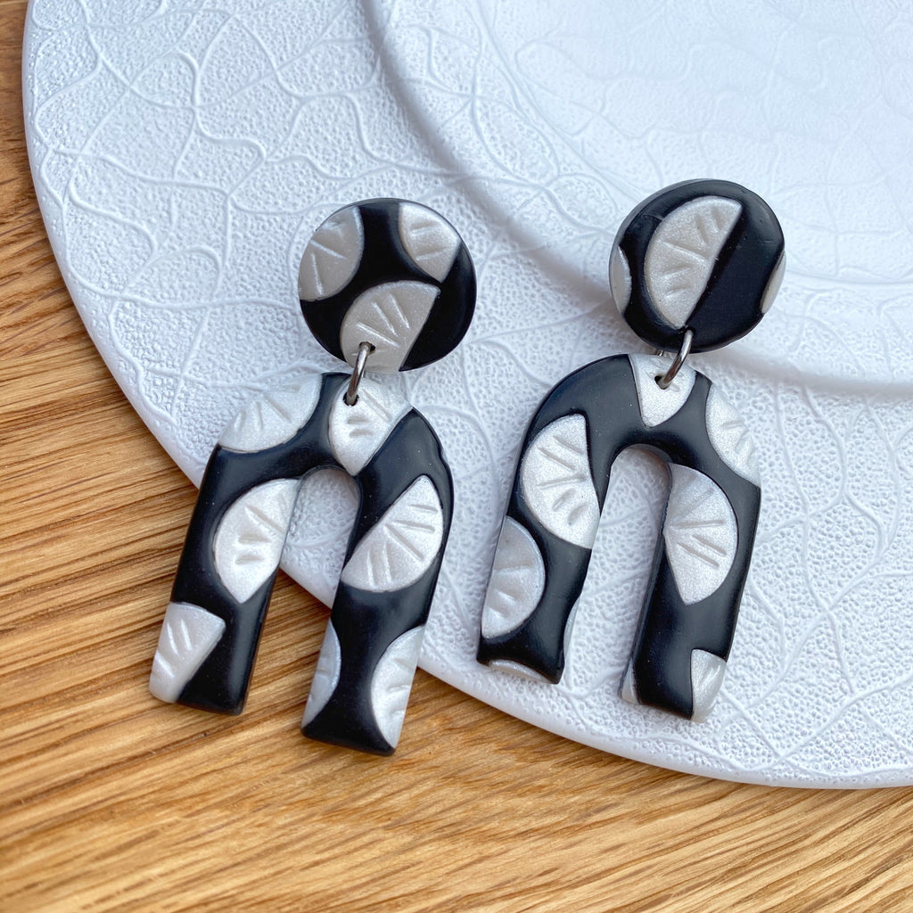 Black with pearl segment pattern statement earrings - horse shoe drop