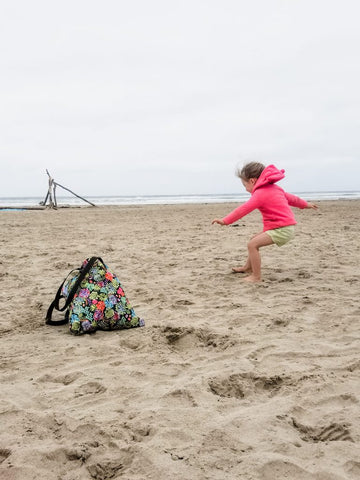 child jumping on a beach with a bag in view