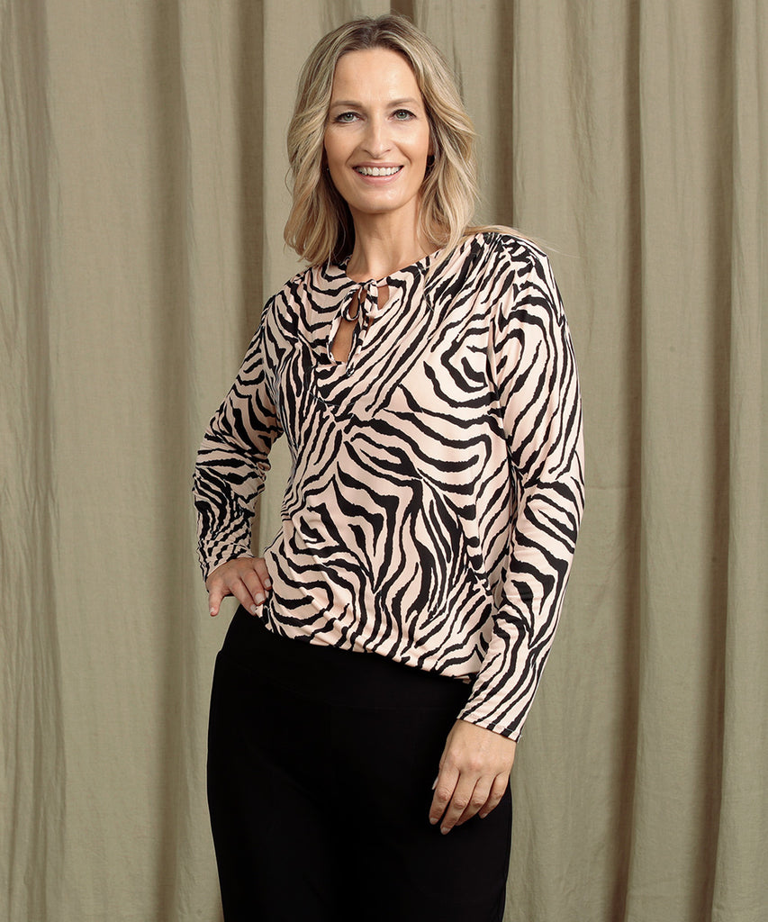 animal print long sleeve top with shoulder gather, neck ties and shirt-tail hemline