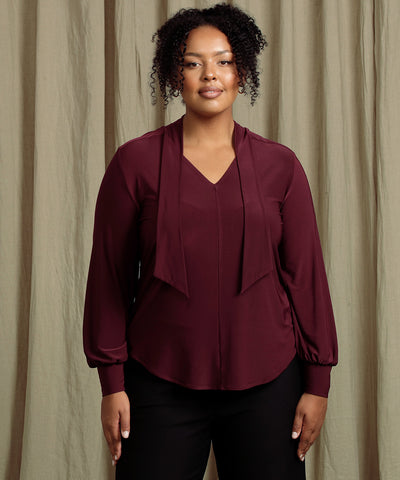 burgundy coloured top with neck tie and long bell sleeves