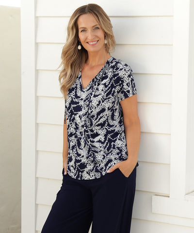 navy and white printed short sleeve summer top with shoulder gather, neck ties and shirt-tail hemline