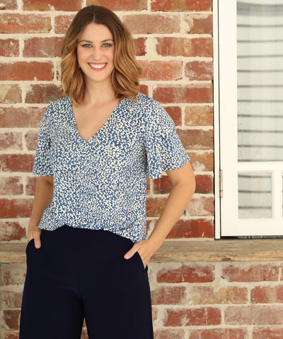 v-neck top with flutter sleeve and shirttail hemline in blue and white print